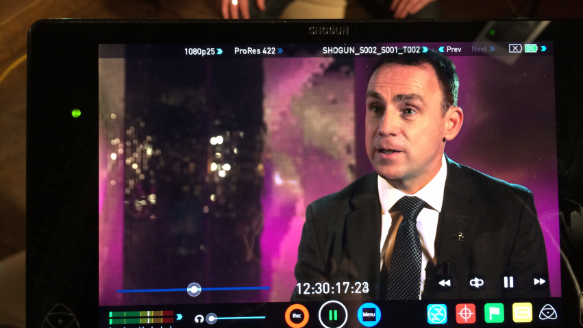 A monitor shows a business man being interviewed in front of a pink background for a corporate video production our company filmed in Glasgow..