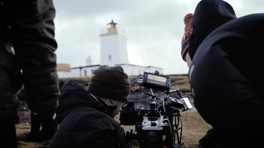 Three people crouch around a camera as they film a lighthouse in Shetland.
