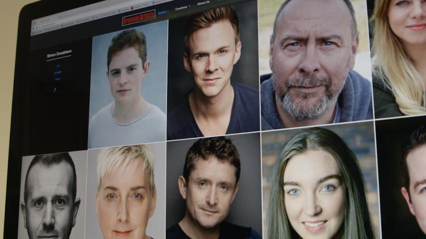 A screen show headshots of various actors.