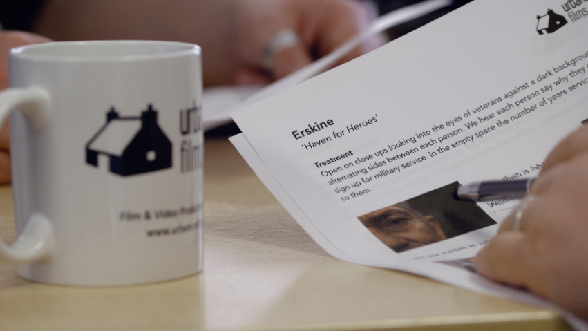 A mug and a close up of a treatment document can be seen.
