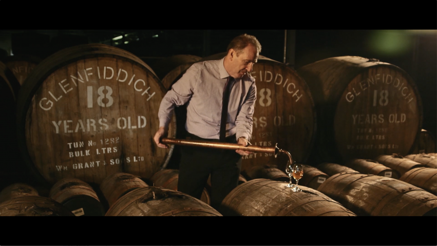Taken from a corporate video production for Glenfiddich, a man stands in front of large whisky casks as he pours a sample into two nosing glasses