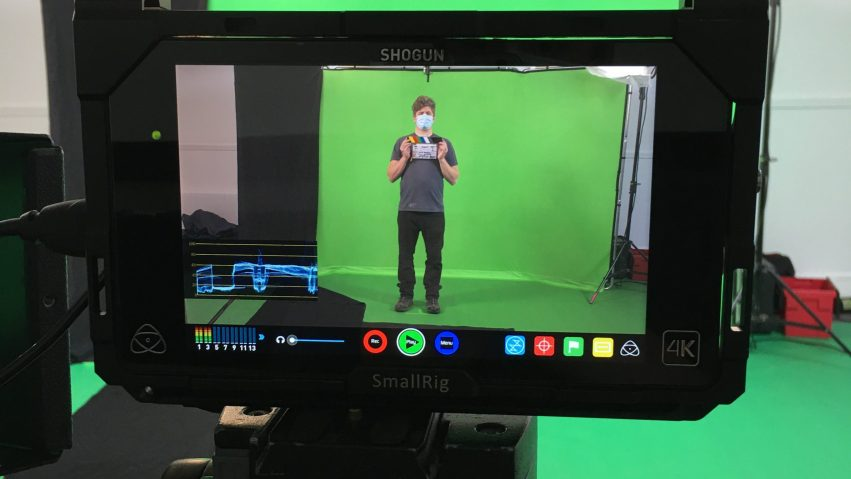 A man stands holding a film slate in a green screen studio.