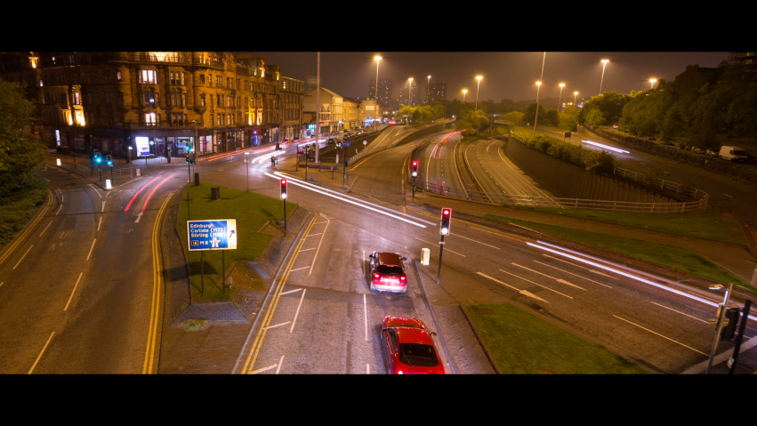 A street scene at night showing roads from an elevated position. Car lights trail across the screen.