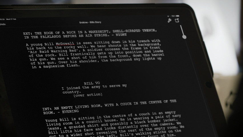 A computer screen shows a script being written in white text against a black background.