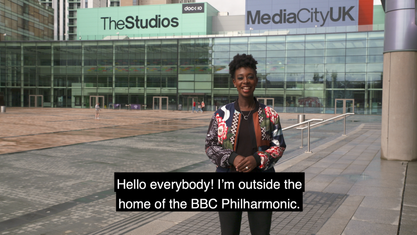 The BBC's YolanDa Brown stands in front of Media City UK and we can see subtitles of what she is saying.