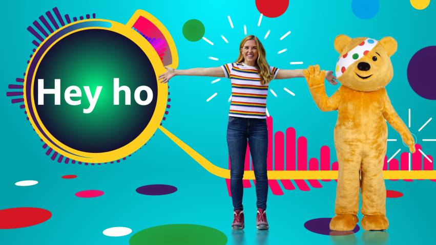 Pudsey Bear and a woman presenter stand in a 3D studio set.