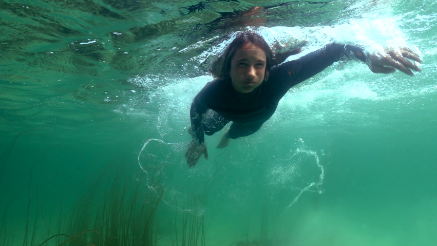 Taken from a film production in Scotland, a young boy in a wetsuit swims underwater.